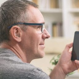 Man with hearing aid uses phone.